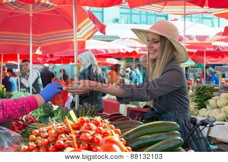 Attractive blonde girl with straw hat paying vegetables on  marketplace.