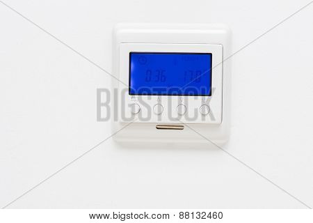 Plastic white thermostat hanging on a plain white wall
