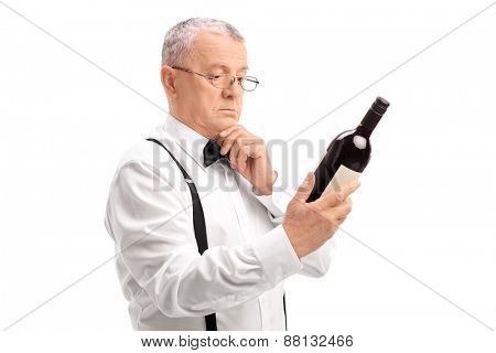 Elegant senior with glasses reading the label on a bottle of a red wine isolated on white background