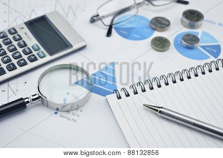 Pen Book Glasses Magnifying Glass And Calculator On Financial Chart And Graph