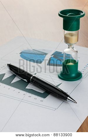 Pen And Hourglass On The Table