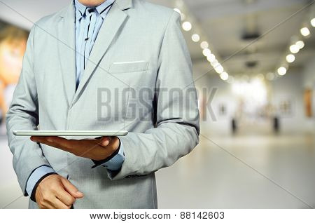 Business Man Using Mobile Tablet In Gallery Art Center Or Museum.