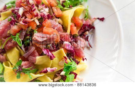 Homemade Tagliatelle With Fresh Tuna Served With Cherry Tomatoes, Radicchio And Arugula