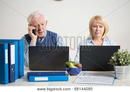 Busy Couple Using Laptops