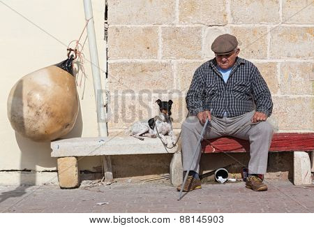 MARSAXLOKK, MALTA - JANUARY 11, 2015: Elderly man with dog sitting on the street bench.