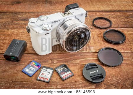 FORT COLLINS, CO, USA, April 17,  2015:  Sony A6000 mirrorless digital camera with a set of filters, memory cards, lens cap and battery on a grunge barn wood table