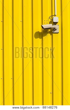 Security camera on a yellow wall