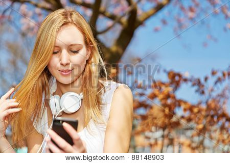 Blonde teenager sitting with smartphone and headphones in a park