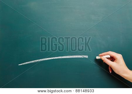 Hand of a teacher drawing white line with chalk on a green chalkboard