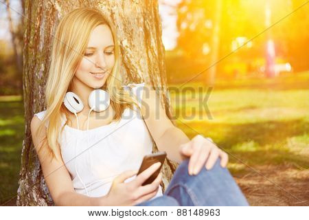 Young woman watching video stream with smartphone in a park in summer