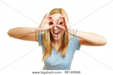 Young happy woman looking with her eyes through her fingers