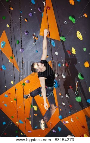 Young man practicing rock-climbing in climbing gym