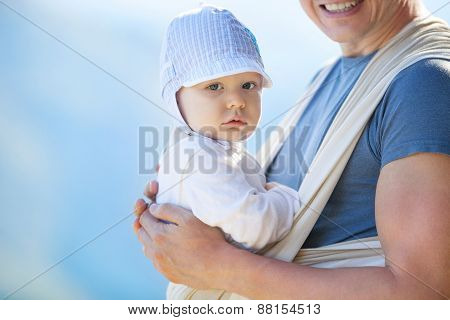 Cute toddler boy in sling, father carrying son