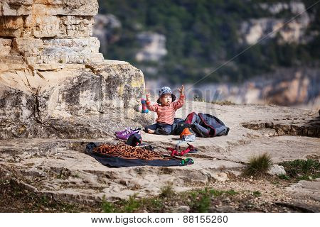 Child of rock climbers playing with climbing rope
