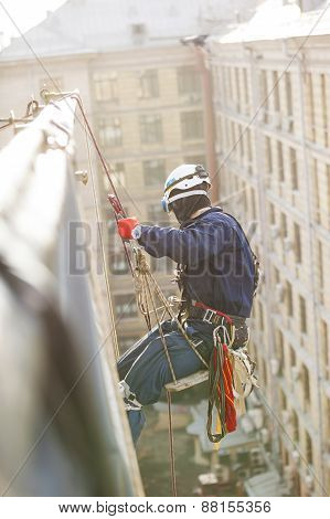 Industrial climber lowering from roof of building
