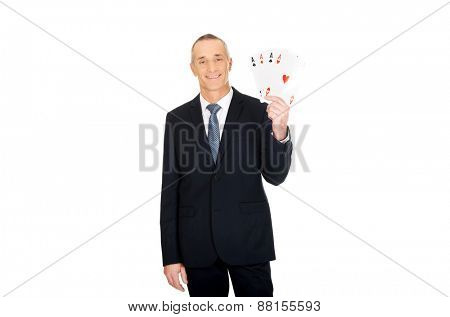 Mature smart businessman with four aces.