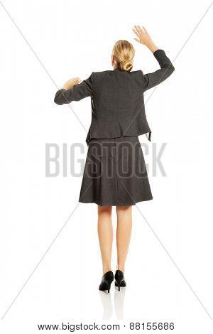 Businesswoman pressing an abstract screen.