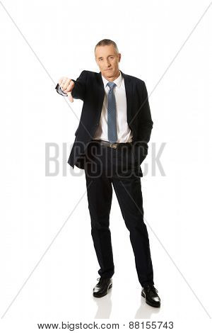 Senior businessman showing thumb down sign.