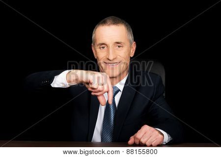 Businessman in office showing small size with fingers.