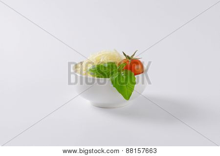 bowl of grated parmesan cheese, cherry tomato and basil on white background
