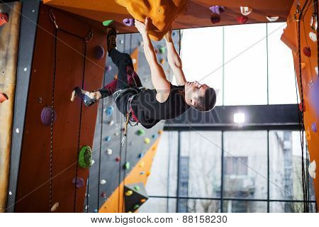 Man practicing top rope climbing in climbing gym