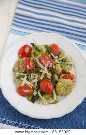 Home made spinach gnocchi with tomatos and parmesan cheese