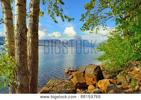 Trees In Front Of The Mcdonald Lake With Mountains In Glacier National Park