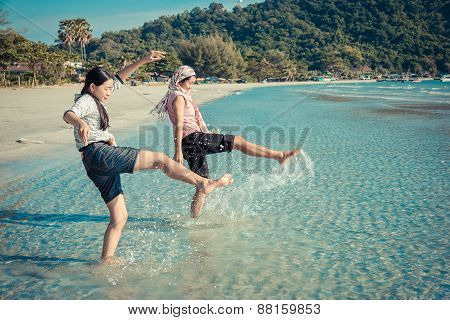 Two Asian Thai Girls Are Kicking The Sea Along The Beach Coast Of Rayong, Thailand In Vintage Color