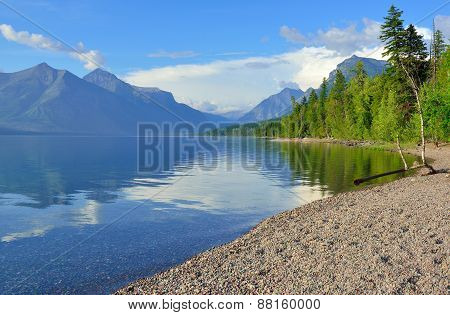 Mountains And The Bank Of Mcdonald Lake In Glacier National Park