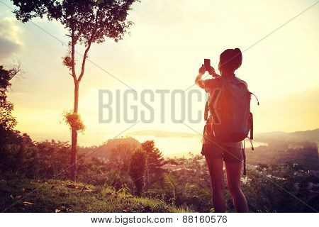 woman hiker taking photo at mountain peak