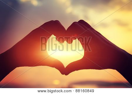 Heart shape making of hands against bright sea sunset and sunny golden way at water