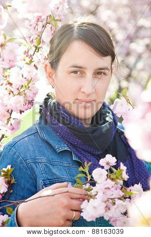 Woman Standing At Blooming Almond Tree