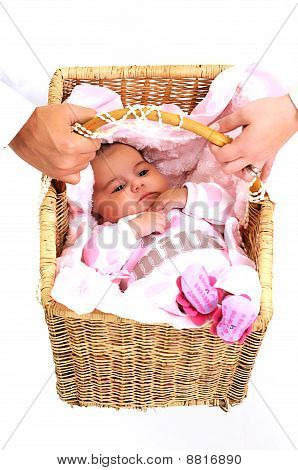 loving parents carrying newborn baby in basket