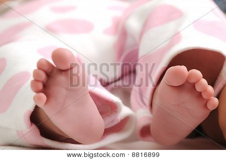close-up photo of baby girl wearing pink dotted clothes and her feet sticking out