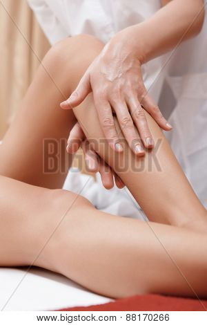 Masseuse works with feet and legs
