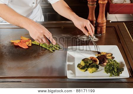 Cook serves meal on a plate