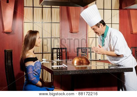 Cook interacts with a female guest
