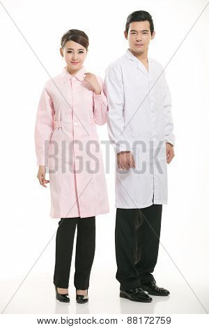 Staff wear coats in front of white background