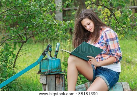 Portrait of reading brunette student girl in summer garden