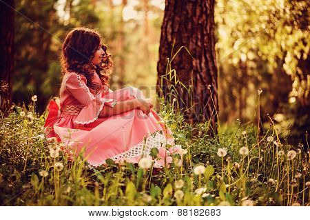 cute curly kid girl in pink princess dress gathering flowers in summer forest