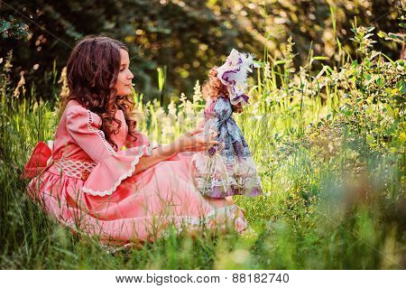 happy child girl in pink fairytale princess dress playing with doll in summer forest