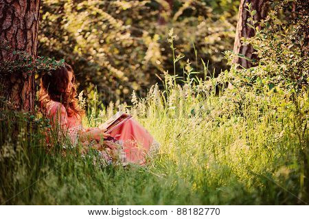 curly girl in pink fairytale princess dress reading book in the forest