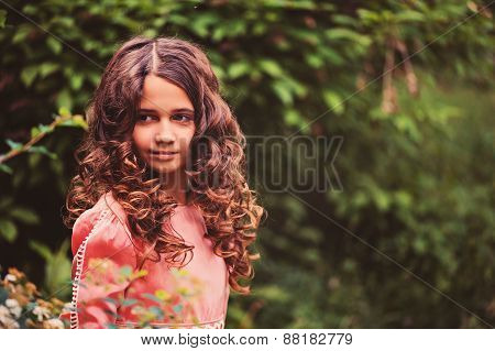 portrait of happy curly girl in pink fairytale princess dress in the forest