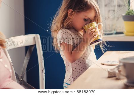 cute toddler girl drinking tea for breakfast at home