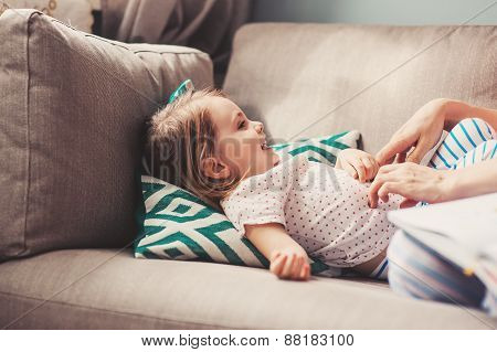 happy mother and toddler daughter having fun at home on the sofa