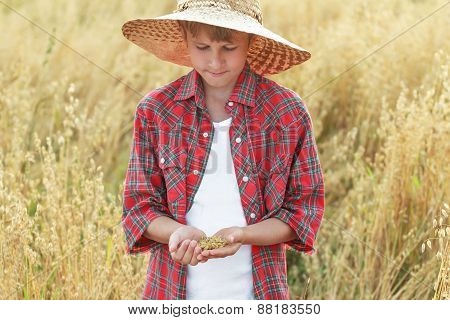 Portrait of teenage farmer boy is checking oat or Avena sativa seeds in cupped palms