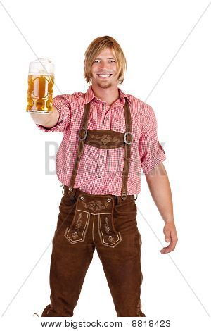 Happy smiling man with leather trousers (lederhose) holds oktoberfest beer stein.