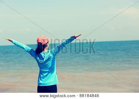 young asian woman open arms seaside stone beach