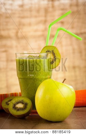 Healthy Green Smoothie Served In A Glass Decorated With Two Color Straws And Kiwi On Wooden Table
