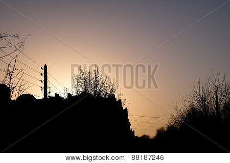 Vanilla coloured rural scene - silhouette of house, trees and wires against sunrise sky